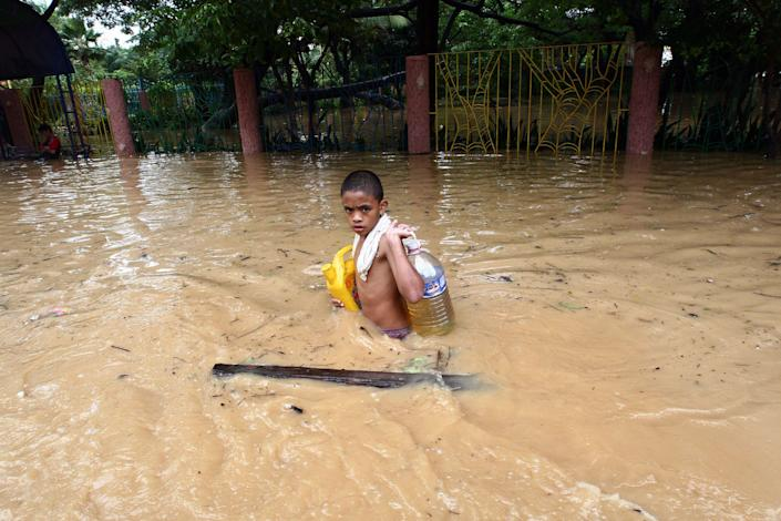 A boy carries supplies through waist-high floodwater in Pasig City in Manila, the capital. On Sept. 30, 2009, in the Philippines, over half a million people are displaced by flooding caused by Tropical Storm Ketsana, which struck on Sept. 26. The storm dumped over a month's worth of rain on the island of Luzon in only 12 hours. The flooding has affected some 1.8 million people, and the death toll has climbed to 246.