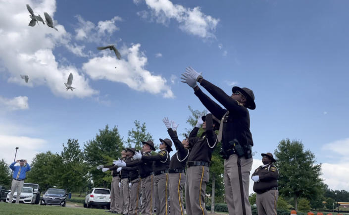 FILE - Sheriff's deputies release white doves for the young victims of a fatal car crash outside a church where the public memorial service was held Thursday, July 15, 2021, in Auburn, Ala. A crash that killed 10 people — including nine children — on a rain-slicked Alabama interstate happened after a tractor-trailer truck slammed into vehicles that had slowed down because of minor crashes, according to a preliminary report released Tuesday, Aug. 3, 2021. (AP Photo/Kim Chandler)