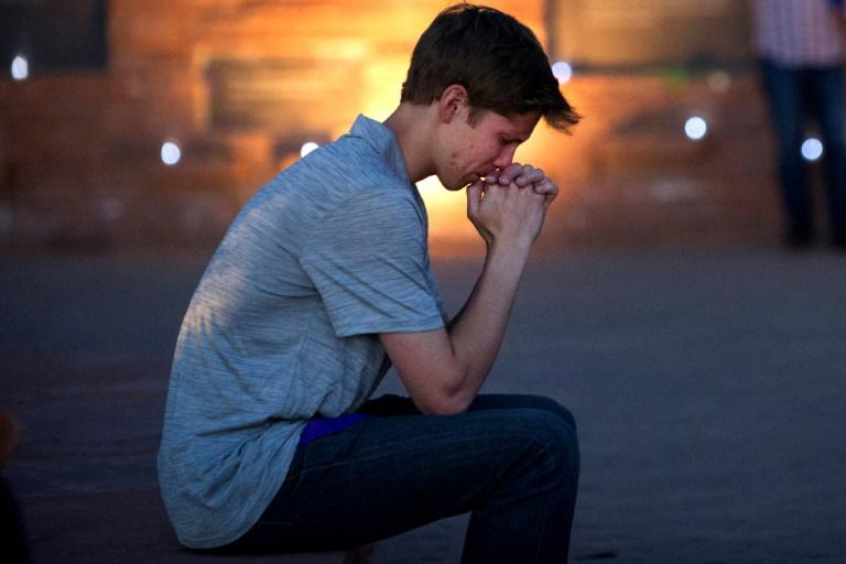 Spencer Greenlee, a Columbine High School senior, prays at a memorial to victims of the shooting