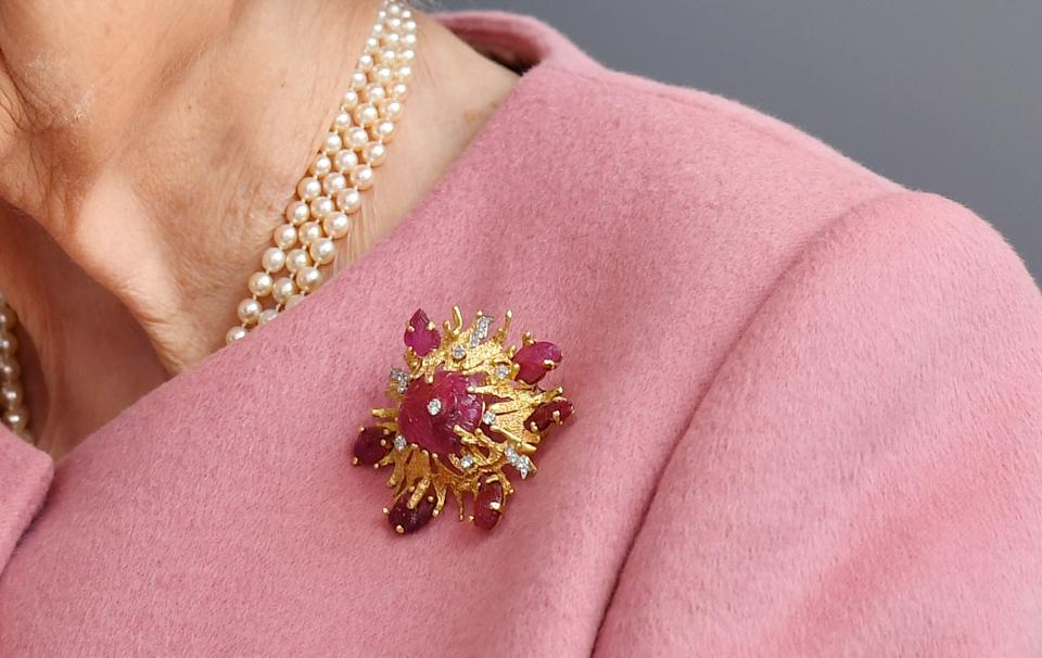 Details of the brooch worn by Queen Elizabeth II during a visit to the Energetics Analysis Centre at the Defence Science and Technology Laboratory (DSTL) at Porton Down, Wiltshire, to view a display of weaponry and tactics used in counter intelligence, and meet staff who were involved in the Salisbury Novichok incident. The brooch was a gift from the Duke of Edinburgh in 1966, for her visit to Porton Down.