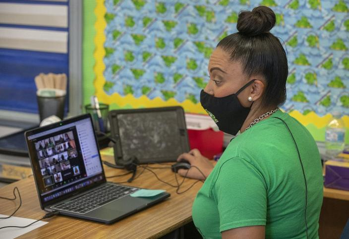 A female teacher wearing a mask conducts her zoom class.