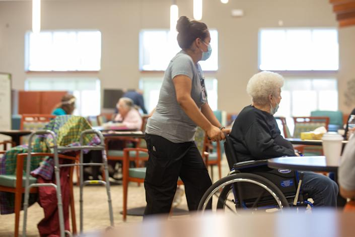 Staff at Midland Care Pace Program of All Inclusive Care for the Elderly, in Topeka, Kan., help those receiving care get around the facility.