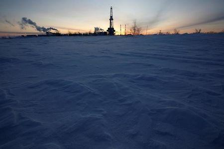 FILE PHOTO: A general view shows an drilling rig at the Lukoil company owned Imilorskoye oil field, as the sun rises, outside the West Siberian city of Kogalym, Russia, January 25, 2016. REUTERS/Sergei Karpukhin/File Photo