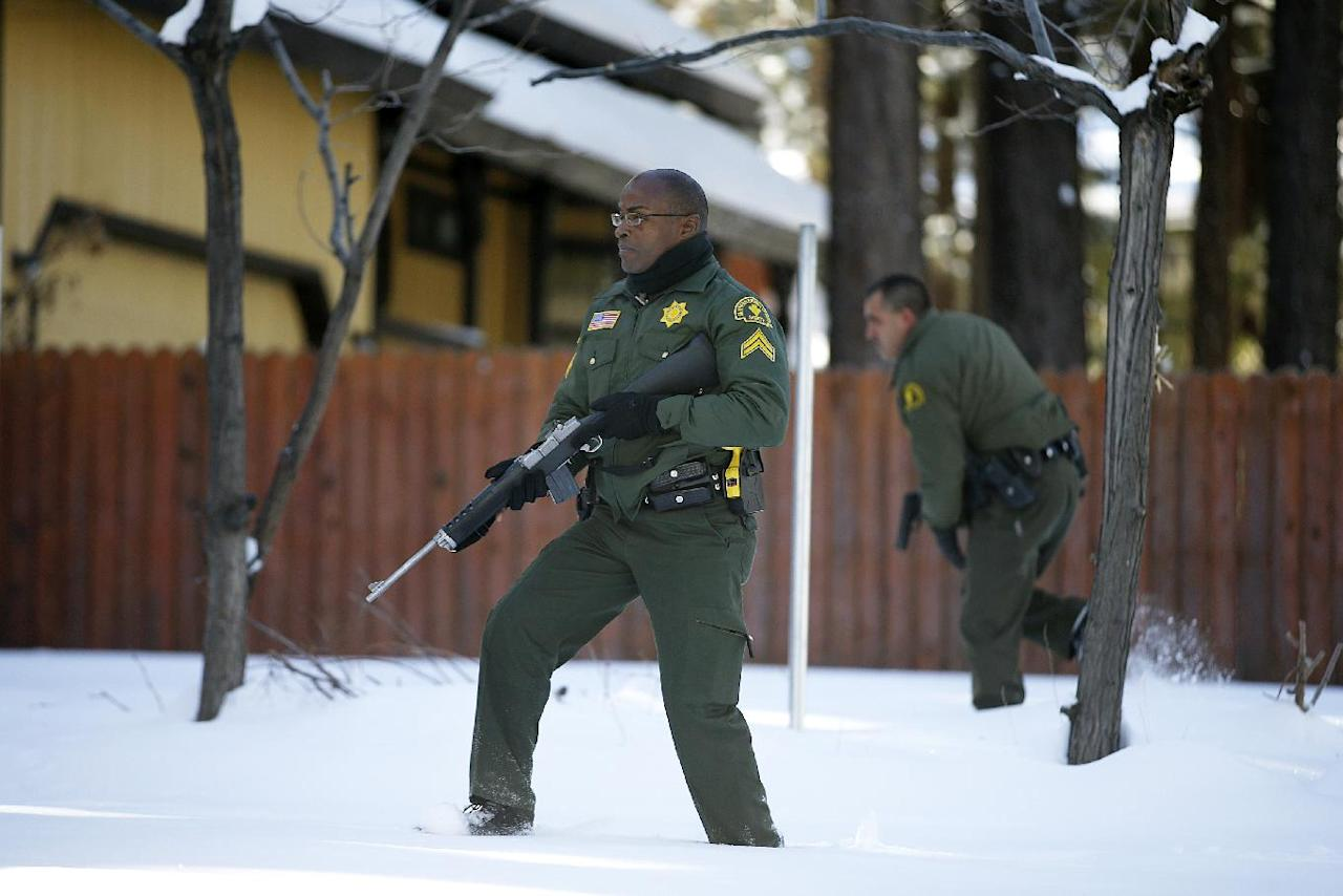 San Bernardino County Sheriff's officers Ken Owens, center, and Bernabe Ortiz search a home for former Los Angeles police officer Christopher Dorner in Big Bear Lake, Calif, Sunday, Feb. 10, 2013. The hunt for the former Los Angeles police officer suspected in three killings entered a fourth day in snow-covered mountains Sunday, a day after the police chief ordered a review of the disciplinary case that led to the fugitive's firing and new details emerged of the evidence he left behind. (AP Photo/Jae C. Hong)