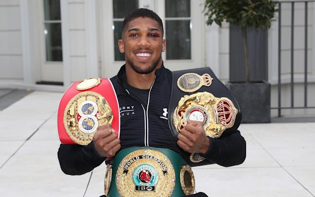 Joshua with IBF, WBA and IBO world title beltsCredit:  LAWRENCE LUSTIG