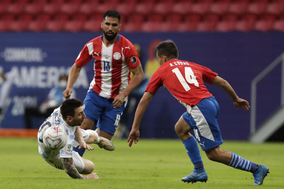 Argentina's Lionel Messi, left, falls during a Copa America soccer match against Paraguay at the National stadium in Brasilia, Brazil, Monday, June 21, 2021. (AP Photo/Eraldo Peres)
