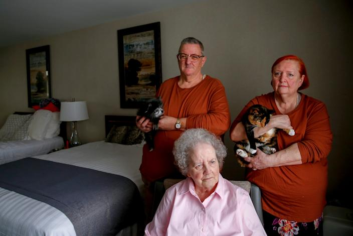Dennis and Denise Schlies, and Shirley Hoover pose for a portrait with their pets Guni the dog and Savannah the cat on Tuesday, Sept. 15, 2020 at a hotel in Salem, Oregon. The family lost their home during the wildfire in Gates, Oregon.