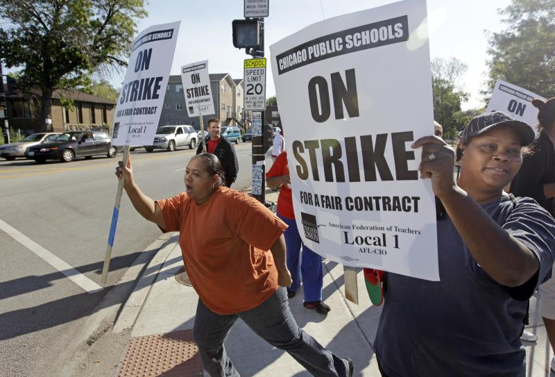 Parents of Chicago public school students, Carmen Brownlee, left, and, Latonya Williams, right, walk a picket line outside Shoop Elementary School in support of striking CPS teachers, Tuesday, Sept. 11, 2012. This is the second day of a strike in the nation's third-largest school district as negotiations by the two sides failed to reach an agreement Monday in a bitter contract dispute over evaluations and job security. (AP Photo/M. Spencer Green)