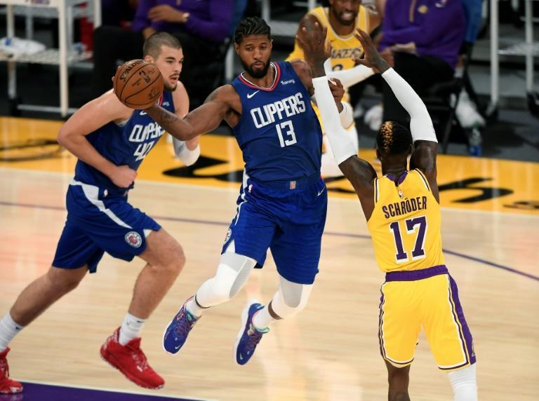 Paul George of the Los Angeles Clippers passes around Dennis Schroder of the Los Angeles Lakers during the season-opening victory over the reigning champions