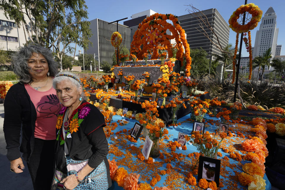 "Ofelia Esparza, 88, with her daughter, Rosanna Esparza Ahrens, left, from East Los Angeles, stand Thursday, Oct. 29, 2020, by their community altar titled ""2020 Memorial to Our Resilience,"" for Day of the Dead at Grand Park in Los Angeles. The mother and daughter Chicana artists have overseen the design of an altar at Grand Park since 2013. It's one of 11 huge altars done in a collaboration between Grand Park and Self Help Graphics, an organization highlighting Chicano and Latino artists and social justice. (AP Photo/Damian Dovarganes)"