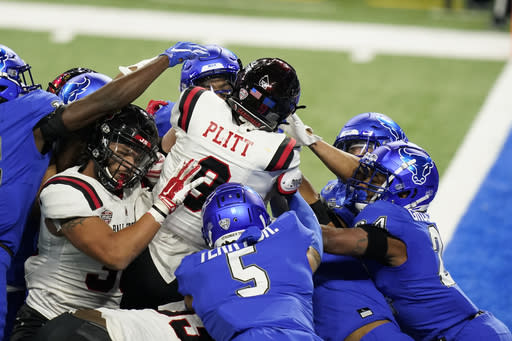 Ball State quarterback Drew Plitt (9) crosses the goal line for a touchdown during the first half of the Mid-American Conference championship NCAA college football game against Buffalo, Friday, Dec. 18, 2020, in Detroit. (AP Photo/Carlos Osorio)