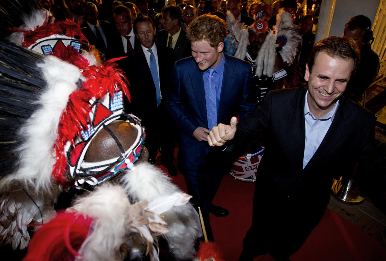 Britain's Prince Harry, center, and Eduardo Paes, mayor of Rio de Janeiro, right, walk past a group of samba dancers in Rio de Janeiro, Brazil, Friday March 9, 2012. Harry is in Brazil at the request of the British government on a trip to promote ties and emphasize the transition from the upcoming 2012 London Games to the 2016 Olympics in Rio de Janeiro. (AP Photo/Victor R. Caivano)