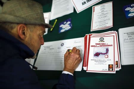 A man put his details on a list while he attends a town hall meeting, sponsored by Brooklyn Borough President Eric Adams, on Ebola and Enterovirus D68 in the courtroom of Brooklyn Borough Hall in New York, October 22, 2014.  REUTERS/Eduardo Munoz