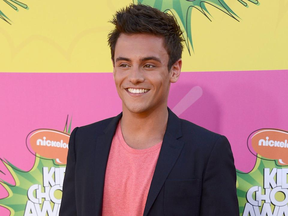 Tom Daley at the Nickelodeon Kid's Choice Awards in 2013 wearing a uit jacket and pink shirt
