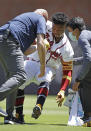 Atlanta Braves' Ronald Acuna Jr. is helped to his feet by trainers after injuring his foot in the seventh inning of a baseball game against the Toronto Blue Jays Thursday, May 13, 2021, in Atlanta. (AP Photo/Ben Margot)