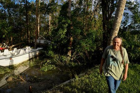 Brenda Hamilton, 62, walks away after seeing her business's boats resting in the trees following Hurricane Irma in Everglades City, Florida, U.S., September 11, 2017. REUTERS/Bryan Woolston