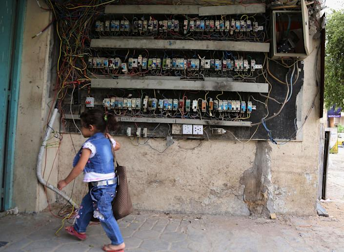 In this photo taken on Sunday, April 27, 2014, a girl walks past an electricity switchboard in Baghdad, Iraq. As parliamentary elections are held Wednesday, more than two years after the withdrawal of U.S. troops, Baghdad is once again a city gripped by fear and scarred by violence. (AP Photo/Karim Kadim)
