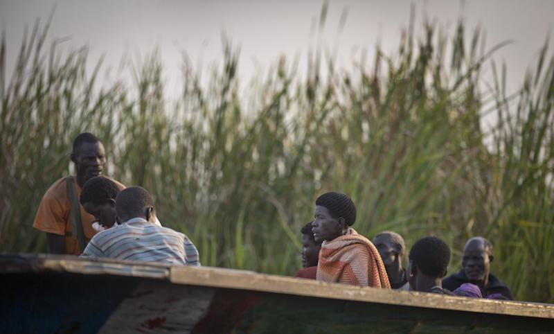 In this photo taken Thursday, Jan. 2, 2014, displaced people arrive by river barge from Bor, some of the thousands who fled the recent fighting between government and rebel forces in Bor by boat across the White Nile, in the town of Awerial, South Sudan. (AP Photo/Ben Curtis)