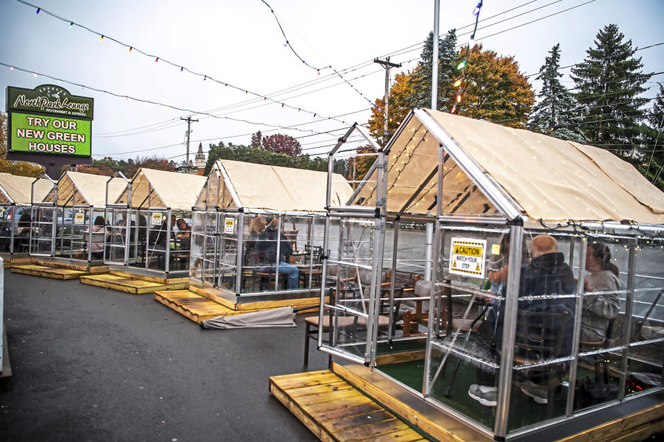 FILE - In this Oct. 20, 2020, file photo, people have dinner in greenhouses used for outdoor dining amid the coronavirus pandemic at North Park Lounge in McCandless, Pa. An increasing number of governors and mayors are imposing restrictions ahead of Thanksgiving for fear that holiday travel and family gatherings will only worsen the record-breaking, coast-to-coast resurgence of the coronavirus. (Alexandra Wimley/Pittsburgh Post-Gazette via AP, File)