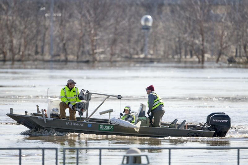 FILE- In this March 16, 2019 file photo, surveyors with the USGS take measurements of the Missouri River in Omaha, Neb., as the river overflows its banks. Nebraska, Iowa, Kansas and Missouri are joining forces for a study that will look for ways the states can limit flooding along the Missouri River and give them information about how wetter weather patterns could require changes to the federal government's management of the basin's reservoirs. The states are pooling their money to pay for half of a $400,000 study with the U.S. Army Corps of Engineers to measure how much water flows down the Missouri River. (AP Photo/Nati Harnik)