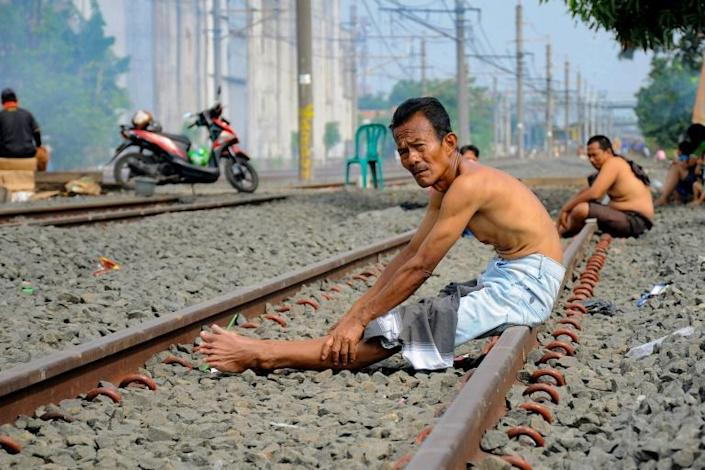 Sunshine and no train today: Indonesians seek out what they believe are the protective solar rays on a train track (AFP Photo/DASRIL ROSZANDI)
