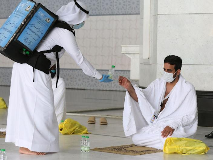 A pilgrim receives water at the Grand Mosque complex in the holy city of Mecca, Saudi Arabia, on July 29, 2020.