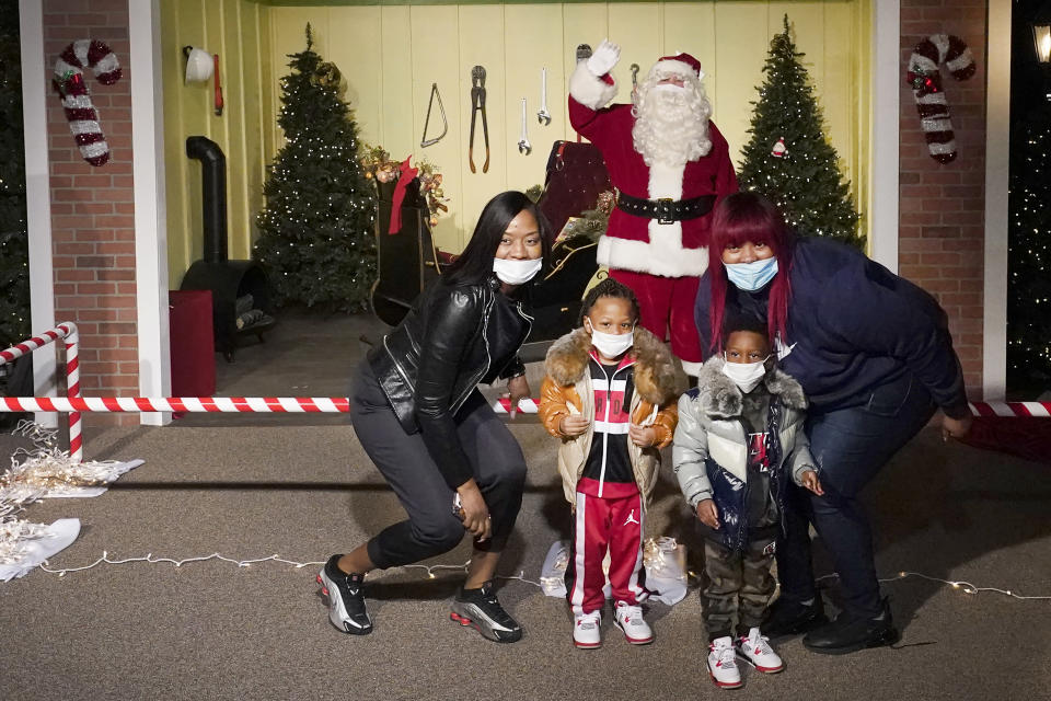 The Bell family poses for a photo with a social distant Santa as they visit Santa's Garage on the roof of a parking deck near Soldier Field in Chicago on Dec. 10, 2020. In this socially distant holiday season, Santa Claus is still coming to towns (and shopping malls) across America but with a few 2020 rules in effect. (AP Photo/Charles Rex Arbogast)