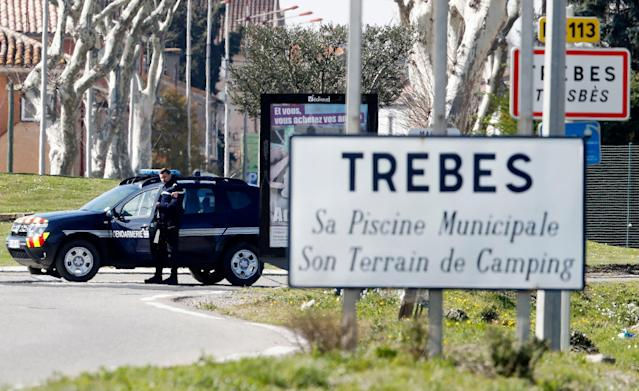 <p>A gendarme secures the perimeter near a roadsign welcoming visitors to Trèbes, where a gunman claiming allegiance to the Islamic State (IS) holding hostages in Trebes, southern France, 23 March 2018. French police are launching a raid on the supermaket where a gunman that allegedly pledged alliance to the IS is holding hostages. Police says at least two people died and dozens were injured in Trebes near Carcassonne. (Photo: Guillaume Horcajuelo/EPA-EFE/REX/Shutterstock) </p>