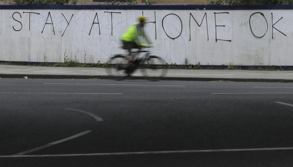 A cyclist passes graffiti as the country continues in lockdown to help curb the spread of the coronavirus, in London, Monday, April 13, 2020. The new coronavirus causes mild or moderate symptoms for most people, but for some, especially older adults and people with existing health problems, it can cause more severe illness or death. (AP Photo/Kirsty Wigglesworth)