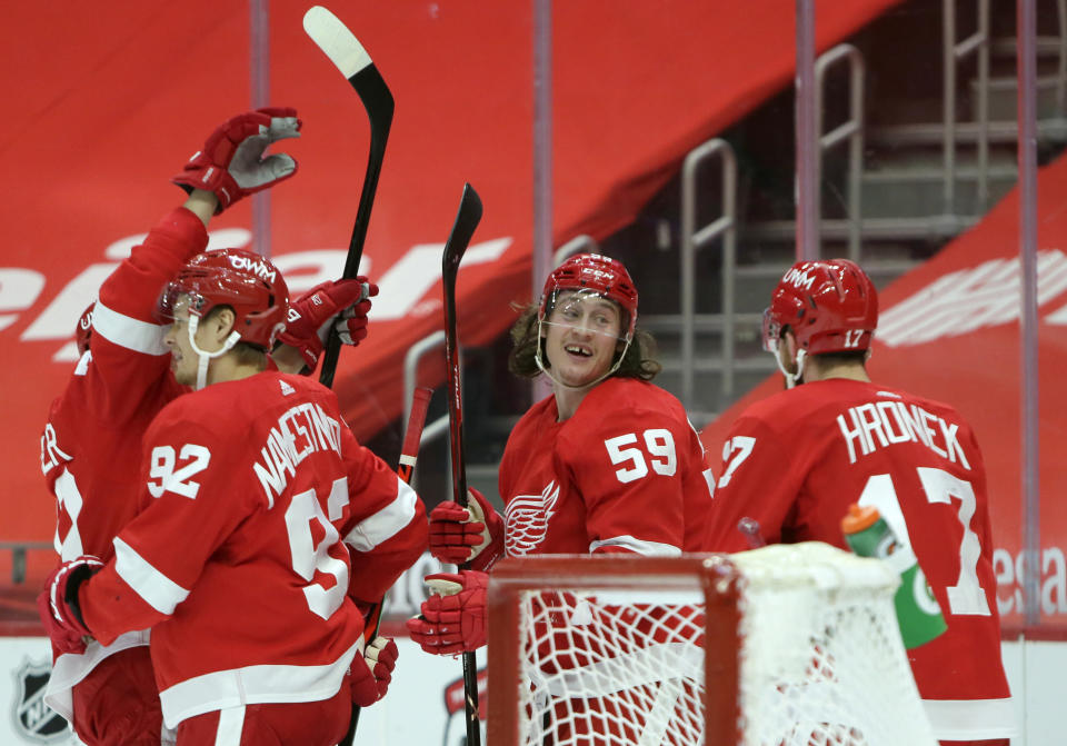 Detroit Red Wings left wing Tyler Bertuzzi (59) celebrates with center Vladislav Namestnikov (92) and defenseman Filip Hronek (17) after scoring the game-winning goal in overtime to defeat the Columbus Blue Jackets in an NHL hockey game Tuesday, Jan. 19, 2021, in Detroit. (AP Photo/Duane Burleson)
