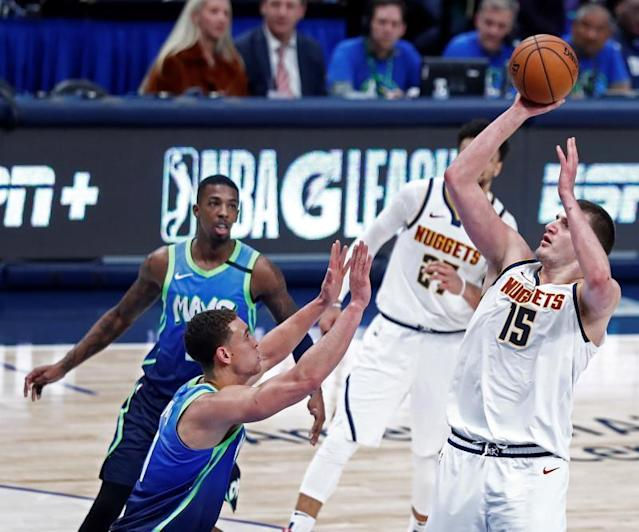 Denver Nuggets player Nikola Jokic of Serbia (R) takes a shot against Dallas Mavericks player Dwight Powell (L) of Canada during the NBA basketball game between the Denver Nuggets and the Dallas Mavericks at the American Airlines Center in Dallas, Texas, USA, 08 January 2020. EFE/EPA/LARRY W. SMITH
