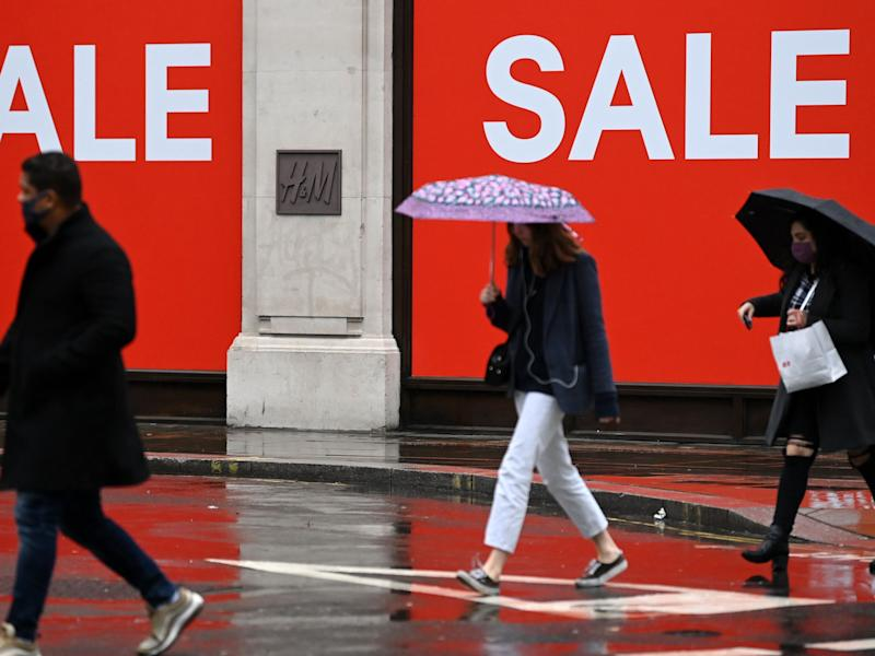 Pedestrians shelter from the rain beneath umbrellas as they pass sale signs outside a H&M shop in London (AFP via Getty Images)