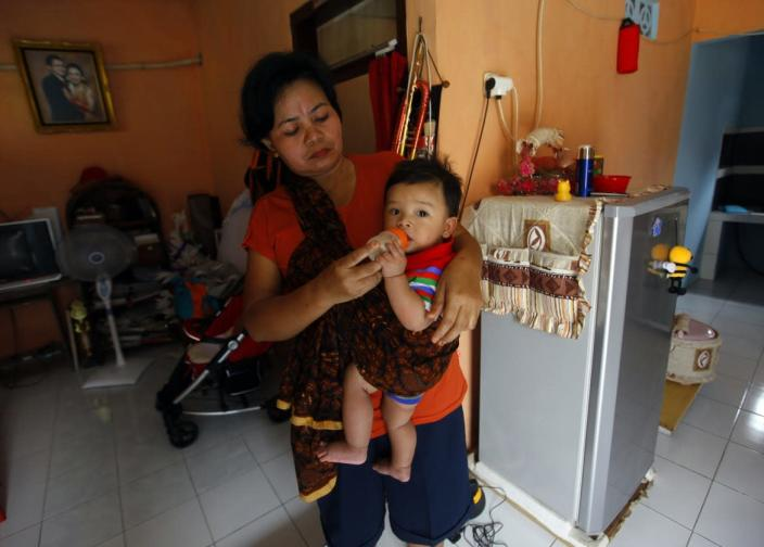 """<div class=""""inline-image__caption""""> <p>A babysitter feeds Abraham Pratama Prasetyo breast milk from his mother, who is working at the office in Jakarta. </p> </div> <div class=""""inline-image__credit""""> Beawiharta/Reuters </div>"""