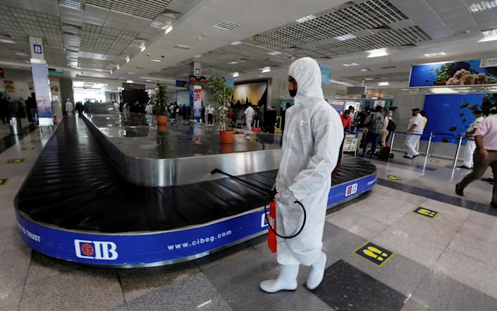 A worker in protective gear sprays disinfectant at Hurghada International Airport in Egypt, as the world cautiously begins to reopen - Reuters
