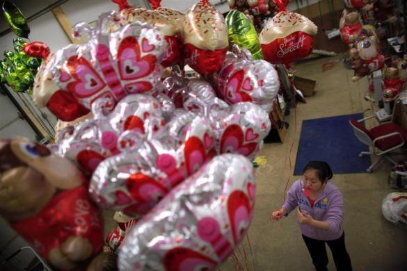 Amy Wang, a foreign exchange student from Shenyang, China,fills up helium balloons for the students at Grant-Deuel School, in Revillo, South Dakota February 13, 2012.