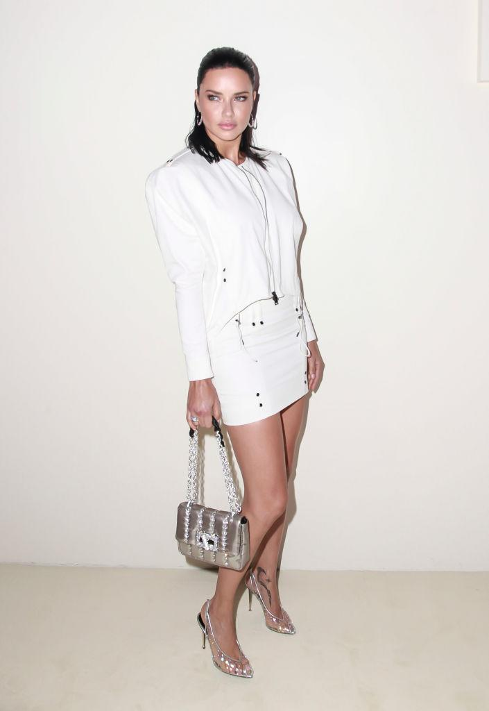 <p>Model Adriana Lima attends Tom Ford's spring/summer 2019 fashion show wearing a white blouson top with a double front zip and a matching low-waisted, belted miniskirt by Ford on Sept. 5, 2018, in New York City. (Photo: Amber De Vos/Patrick McMullan via Getty Images) </p>