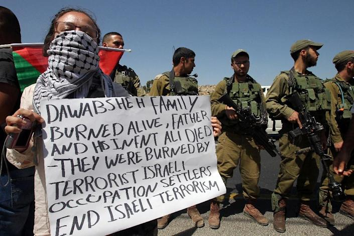 Palestinian and foreign activists on August 8, 2015 during a demonstration to condemn the arson attack in the West Bank village of Duma that killed an 18-month-old child and his father (AFP Photo/Hazem Bader)