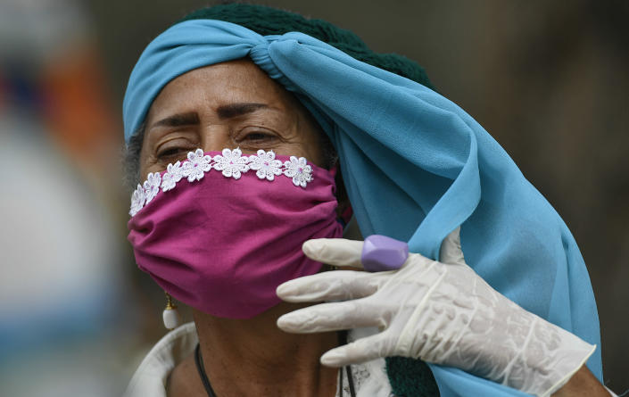 An elderly woman wearing a protective face mask and disposable gloves adjusts her headscarf as she takes a walk outside at a nursing home amid the spread of the new coronavirus in Caracas, Venezuela, Saturday, May 2, 2020. (AP Photo/Matias Delacroix)