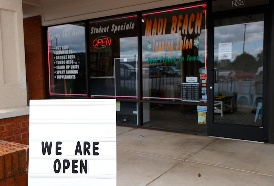 """A sign says that Maui Beach Tanning Salon is open on April 24, in Marietta, Ga., where Gov. Brian Kemp announced some """"nonessential"""" businesses could reopen. (Kevin C. Cox/Getty Images)"""