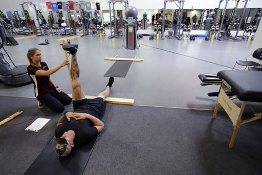 In this Oct. 8, 2018, photo, former NFL football player Nick McDonald raises his leg as he works with Cienna Collins during a range of motion evaluation at Exos in Carlsbad, Calif. McDonald played for the Green Bay Packers, New England Patriots, San Diego Chargers, and Cleveland Browns during his time playing football in the NFL. (AP Photo/Gregory Bull)