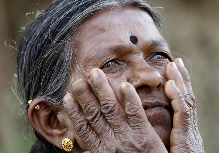 In this Dec. 5, 2012 photo, Gangarangamma, 65, gestures as she speaks to The Associated Press near the land, she and her husband farmed for decades which the records show is registered to the government, a sign the land remained in dispute, in village Karadigere Kaval, 85 kilometers (53 miles) from Bangalore, India. For years, Karnataka's land records were a quagmire of disputed, forged documents maintained by thousands of tyrannical bureaucrats who demanded bribes to do their jobs. In 2002, there were hopes that this was about to change. (AP Photo/Aijaz Rahi)