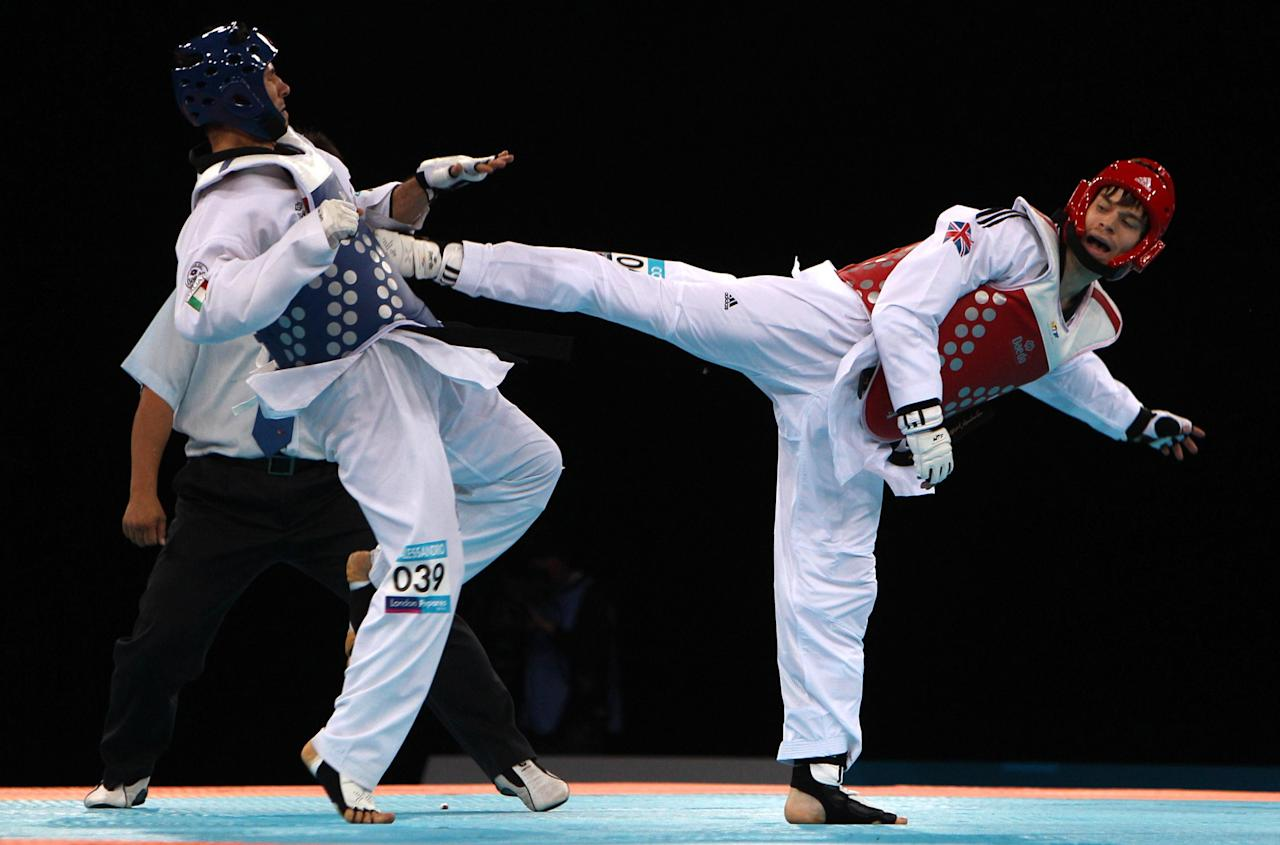 In this photo taken Sunday, Dec. 4, 2011, Britain's Aaron Cook, right, fights with Italy's Gianluca D'Alessandrio in the 80kg preliminary round of a London 2012 test event at the Excel Arena, London. (AP Photo/PA, Nick Potts) UNITED KINGDOM OUT, NO SALES, NO ARCHIVE