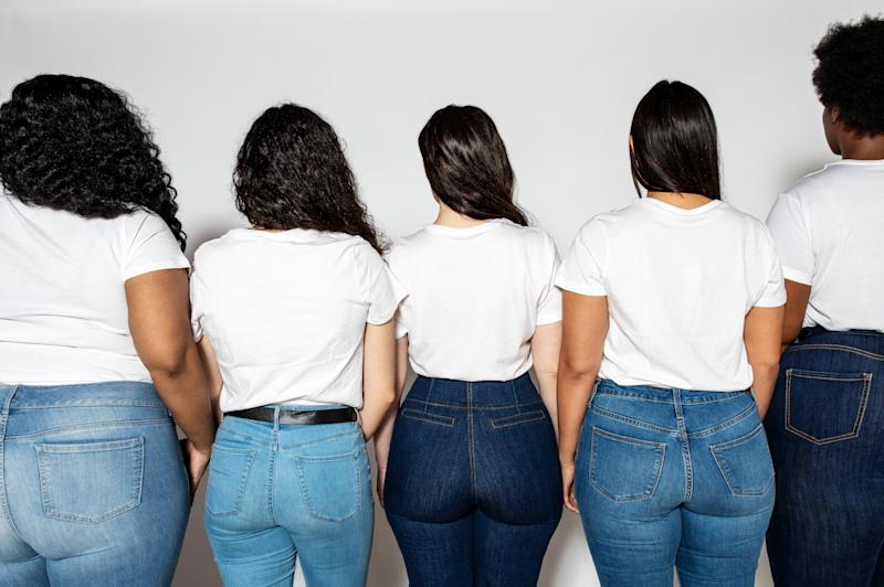 Rear view shot of different size women in white t-shirt and blue jeans. Multiracial women standing together over white background.