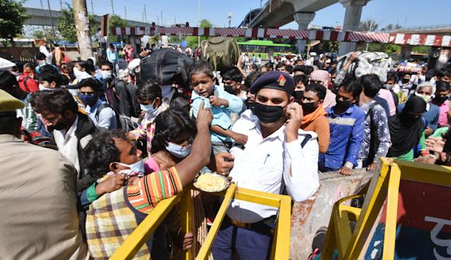 NEW DELHI, INDIA - MARCH 28: A traffric police personnel holds a child as a wave of migrants workers try to Kaushambi Roadways Bus Stand on Day 4 of the 21 day nationwide lockdown -- to check the spread of coronavirus, at Delhi UP border (opposite Anand Vihar Bus Stand, on March 28, 2020 in New Delhi, India. (Photo by Ajay Aggarwal/Hindustan Times via Getty Images)