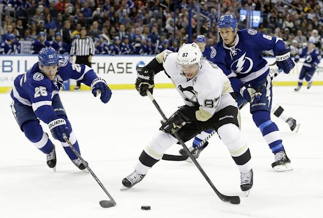 Pittsburgh Penguins center Sidney Crosby (87) skates between Tampa Bay Lightning defensemen Matt Carle (25) and Sami Salo (6), of Finland, during the first period of an NHL hockey game on Friday, Nov. 29, 2013, in Tampa, Fla. (AP Photo/Chris O'Meara)