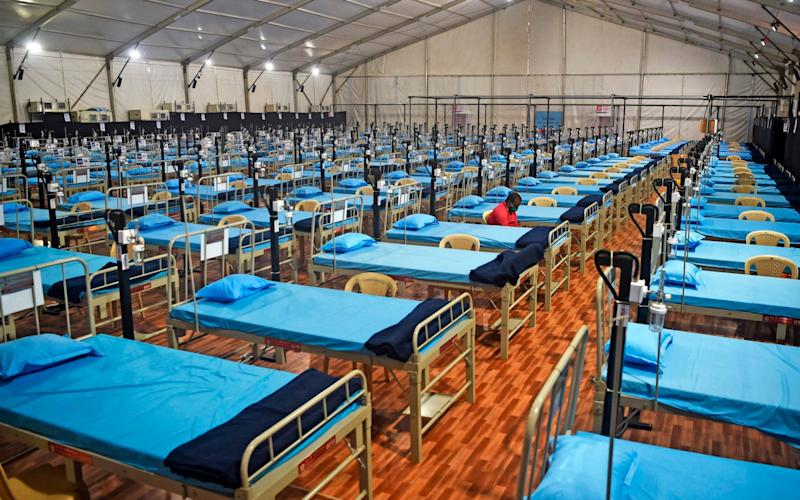 A man sits next to beds at a newly built hospital to treat Covid-19 coronavirus patients at the Mahalaxmi Racecourse - AFP