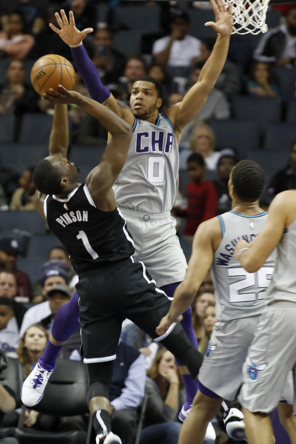 Brooklyn Nets' Theo Pinson (1) tries to get a shot off over Charlotte Hornets' Miles Bridges (0) during the second half of an NBA basketball game in Charlotte, N.C., Friday, Dec. 6, 2019. The Nets won 111-104. (AP Photo/Bob Leverone)