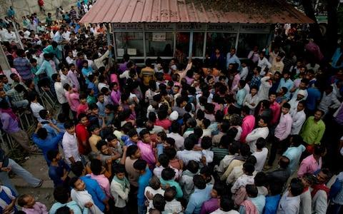 <span>Indian migrant workers wait outside the government transport yard as they seek to buy bus tickets out of Kashmir</span> <span>Credit: AP </span>