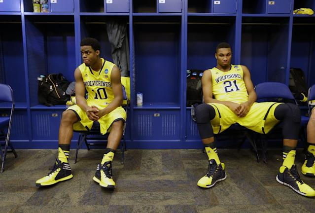 Michigan's Derrick Walton Jr. (10) and Zak Irvin (21) sit in the locker room after an NCAA Midwest Regional final college basketball tournament game against Kentucky Sunday, March 30, 2014, in Indianapolis. Kentucky won 75-72 to advance to the Final Four. (AP Photo/Michael Conroy)
