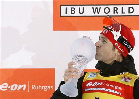 Ole Einar Bjorndalen of Norway kisses his World Cup trophy after winning this season's men's 12.5 km pursuit at the Biathlon World Cup Final in the Siberian town of Khanty-Mansiysk